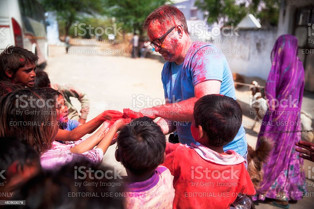 Tourist giving out Holi Powder to kids. stock photo