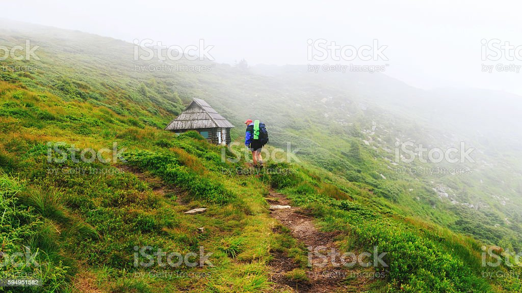 Tourist goes along mountain trail to the small wooden house stock photo