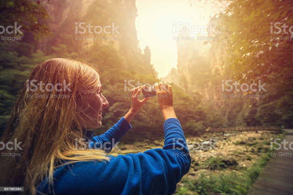 Tourist hiking take smart phone picture-Zhangjiajie national park stock photo