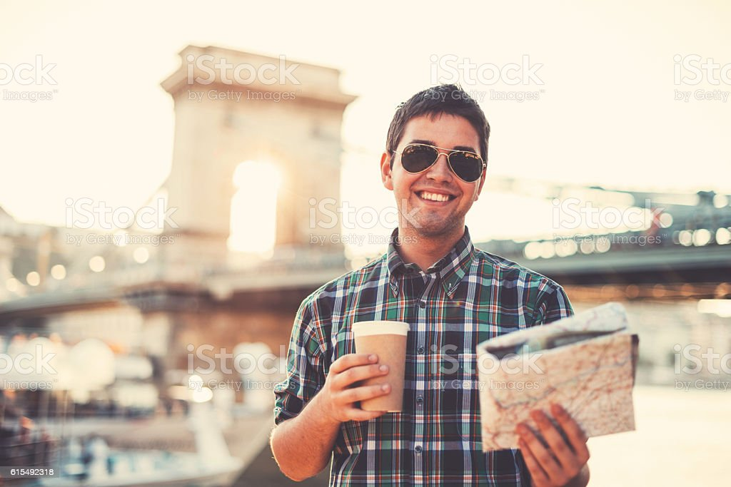 Tourist holding cup of coffee and map stock photo
