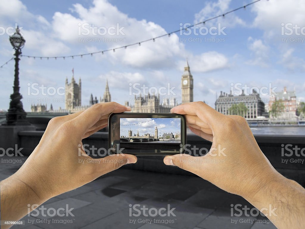tourist holds up camera mobile at big ben stock photo
