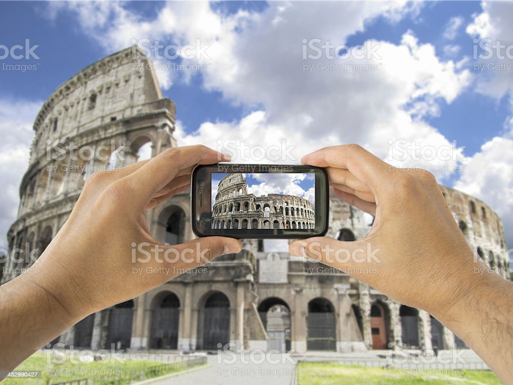 tourist holds up camera mobile at coliseum in Rome stock photo