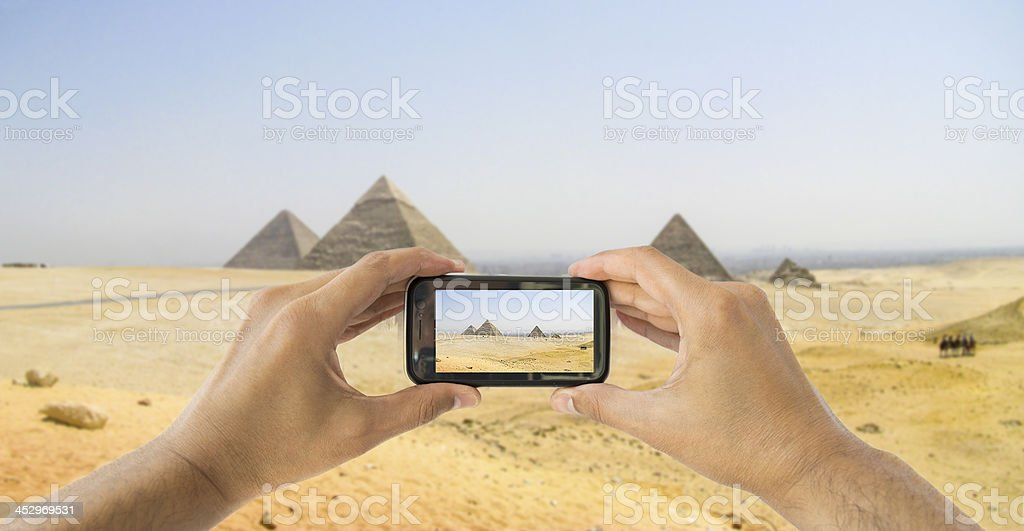 tourist holds up camera mobile at  pyramids stock photo