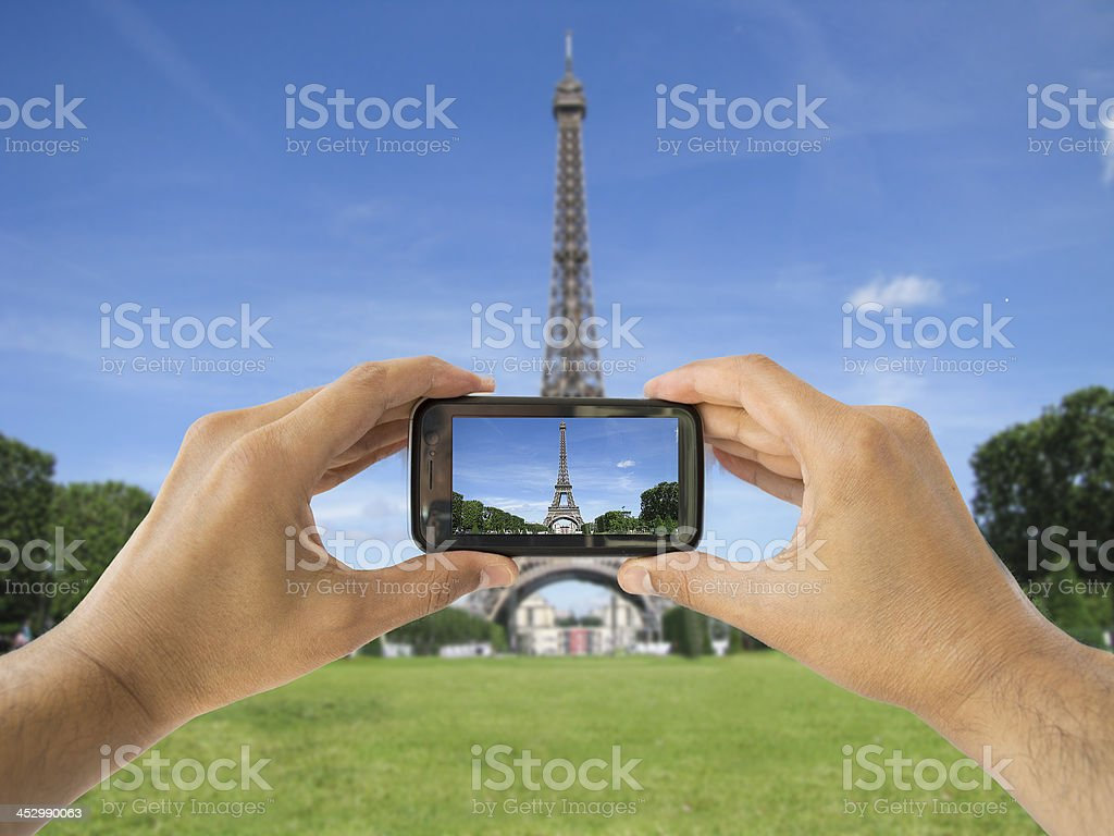 tourist holds up camera phone at   eiffel tower stock photo