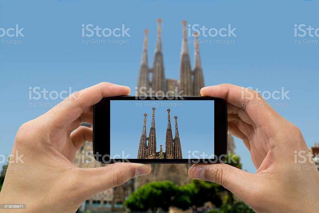 tourist holds up camera phone at sagrada familia stock photo