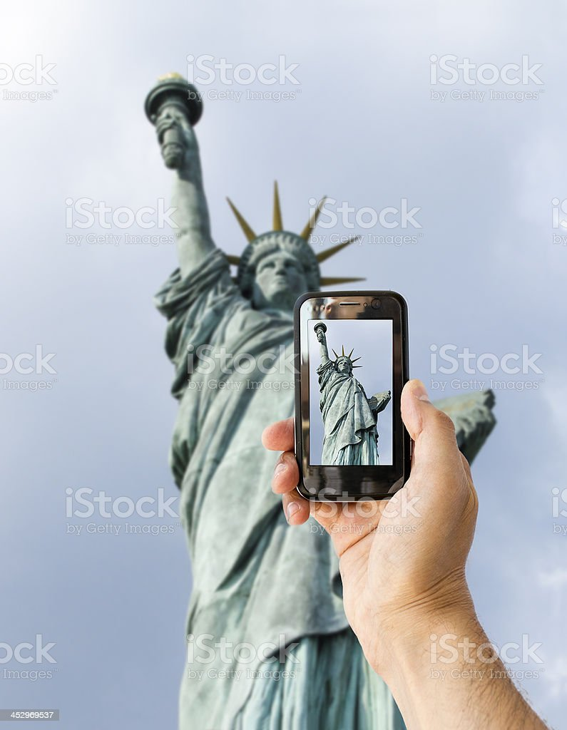 tourist holds up camera phone at  statue of liberty stock photo
