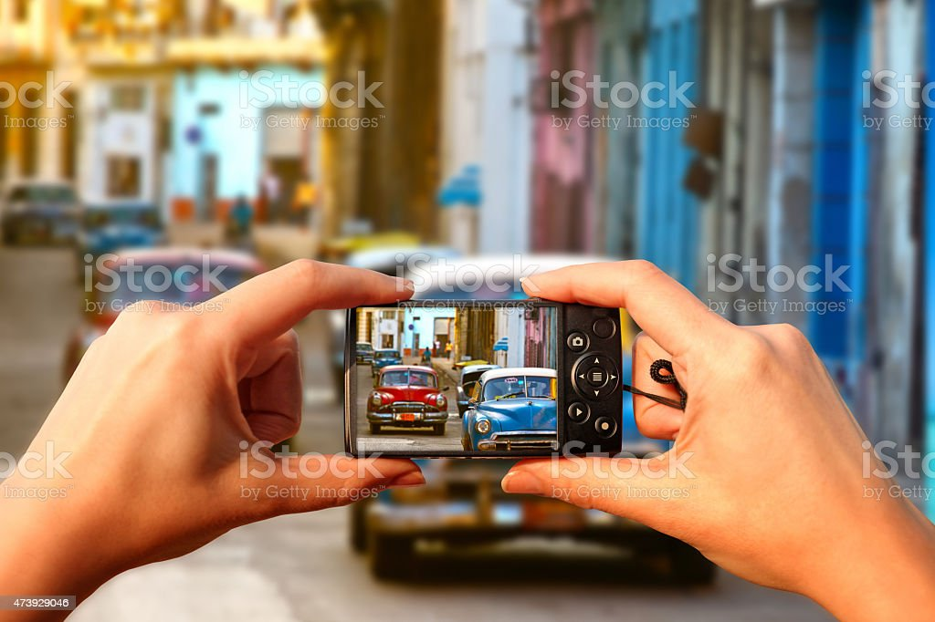 Tourist in Cuba: woman photographing old american cars in Havana stock photo