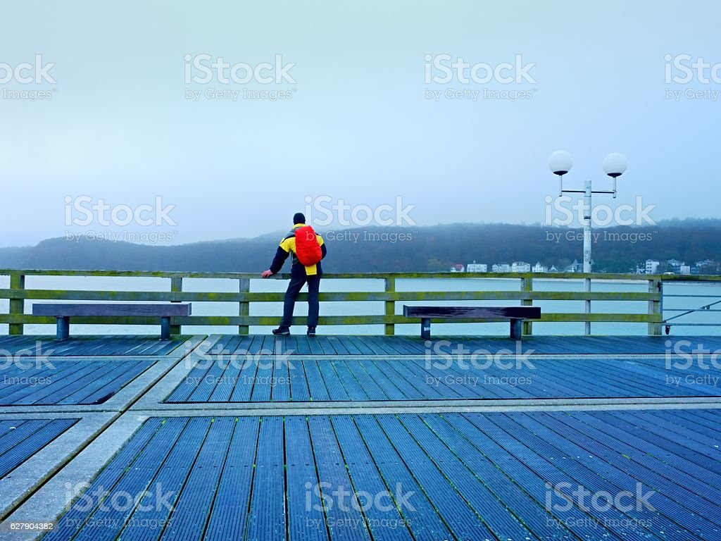 Tourist in depression, autumn mist on wooden pier above sea. stock photo