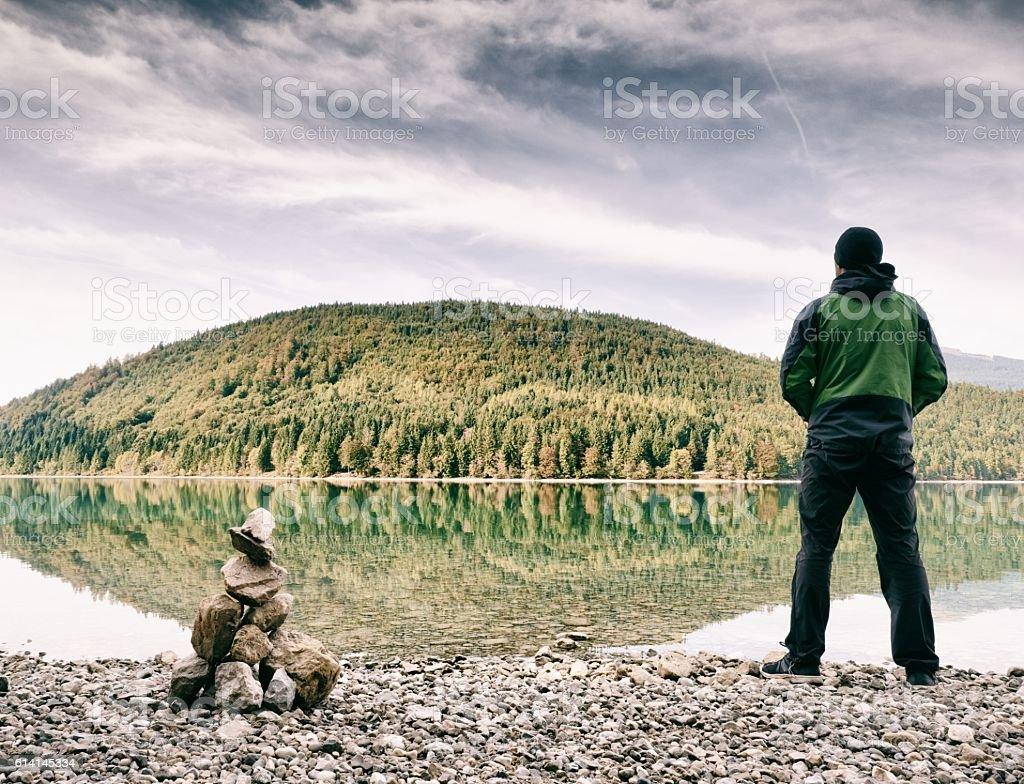 Tourist in green black clothing and cap, Alpine lake beach. stock photo