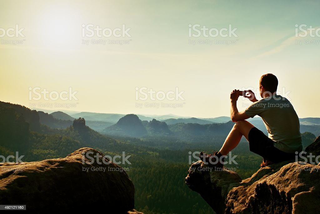 Tourist in grey t-shirt takes photos with phone. Dreamy hills stock photo