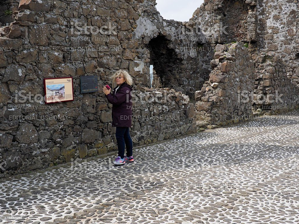 tourist in the dunluce castle stock photo