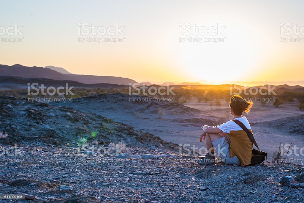 Tourist looking at view at sunset, Namib desert stock photo