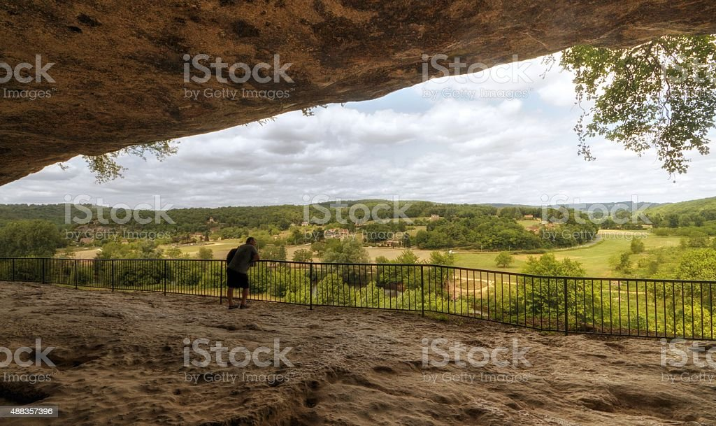 Tourist looking at view from cave at Roque Saint Christophe stock photo
