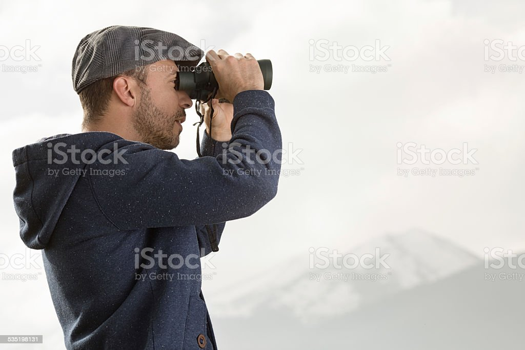 Tourist looking through binoculars stock photo