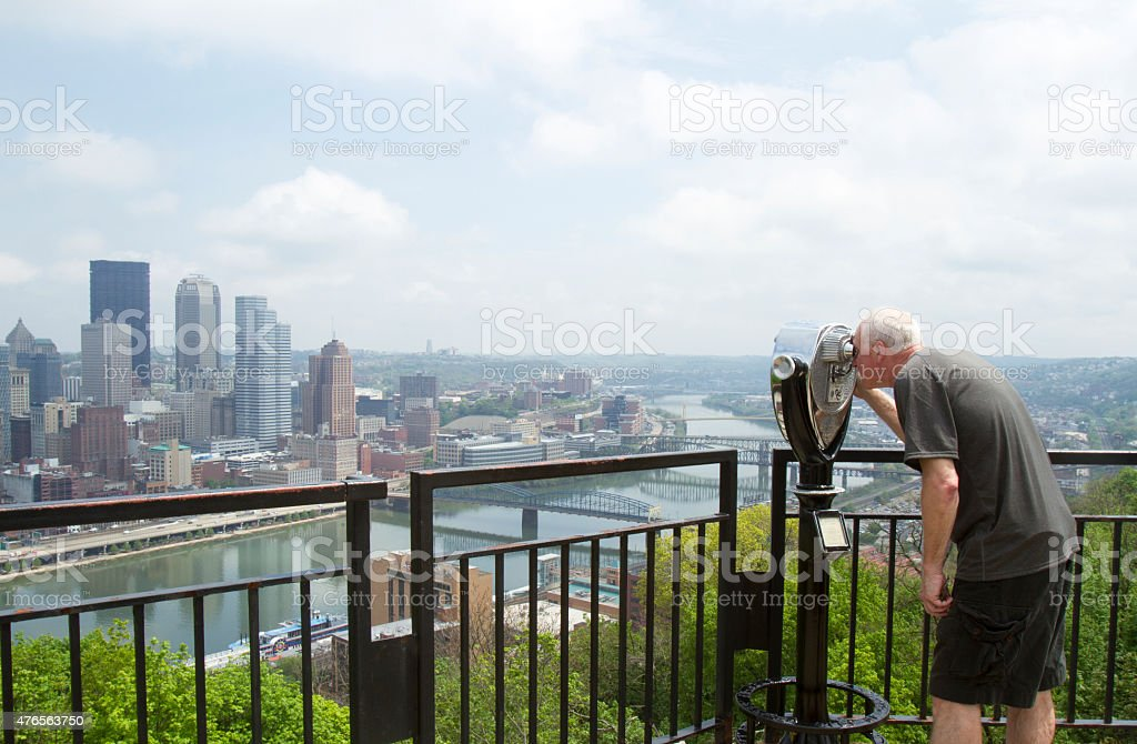 Tourist looking through viewfinder stock photo
