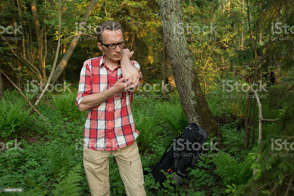 tourist lost in woods fighting the mosquitoes. stock photo