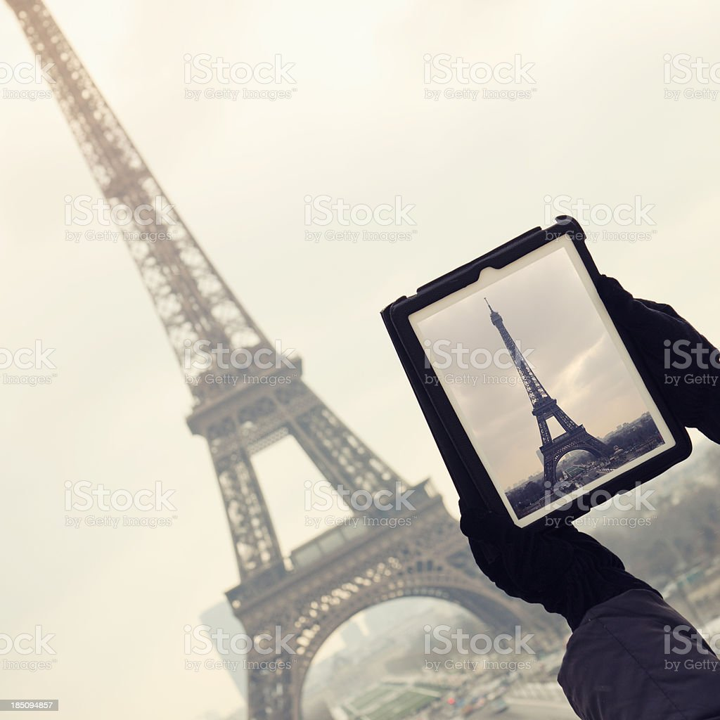 Tourist make a photo of Tour Eiffel with digital tablet royalty-free stock photo
