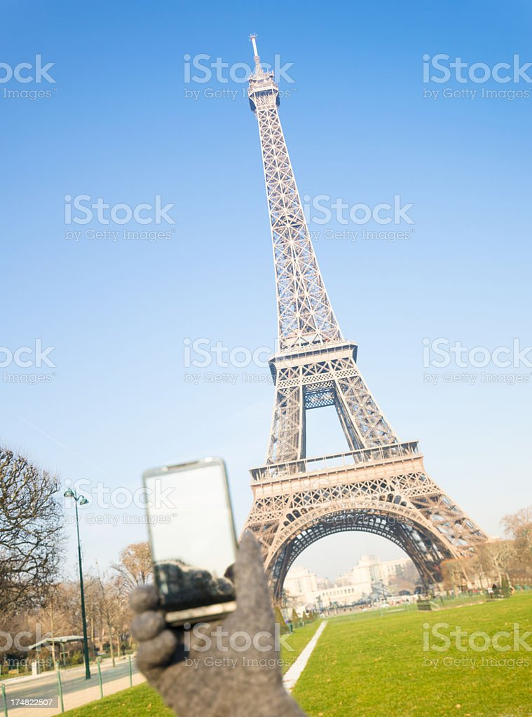 Tourist make a photo of Tour Eiffel with smartphone royalty-free stock photo