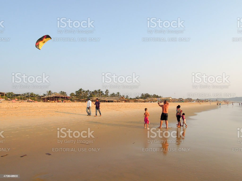 Tourist making fly a kite on the beach of Candolim stock photo