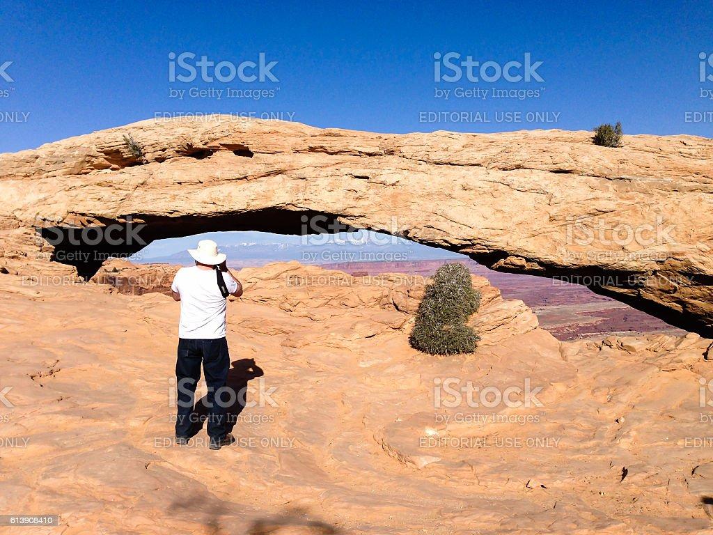 Tourist man, Mesa Arch, Canyonlands, blue sky stock photo