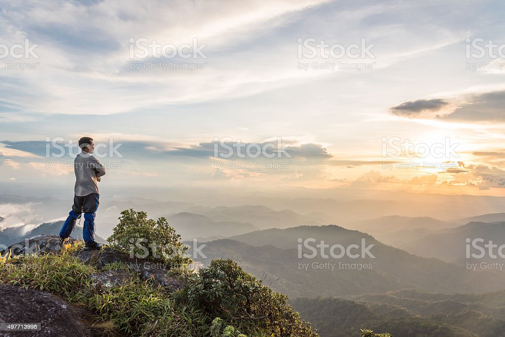 tourist man on top of mountain enjoying valley view stock photo
