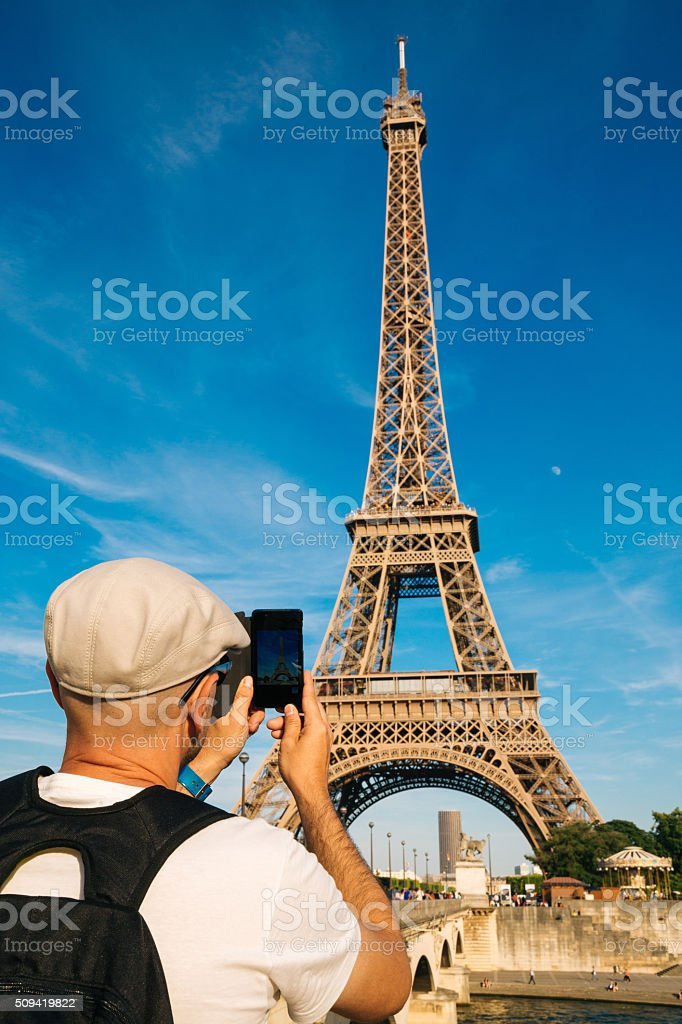Tourist man taking pictures of the Eiffel Tower stock photo