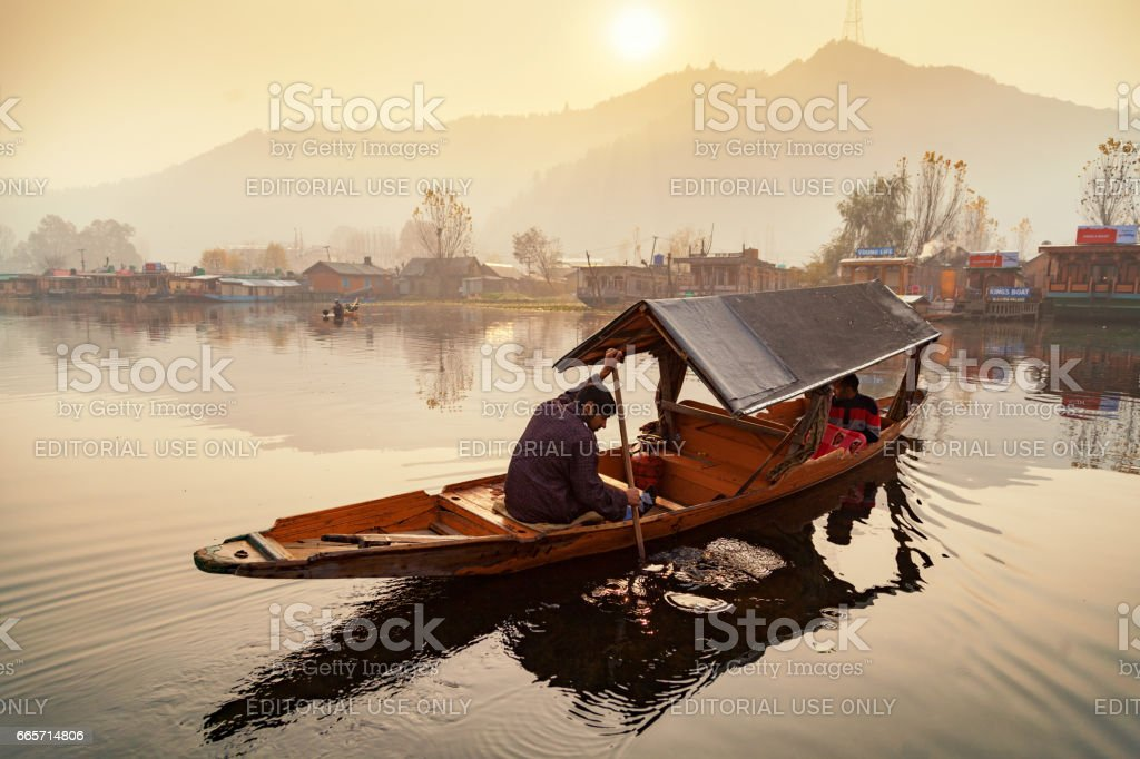 Tourist move around in a shikara boat while sunsets in background at Dal Lake stock photo