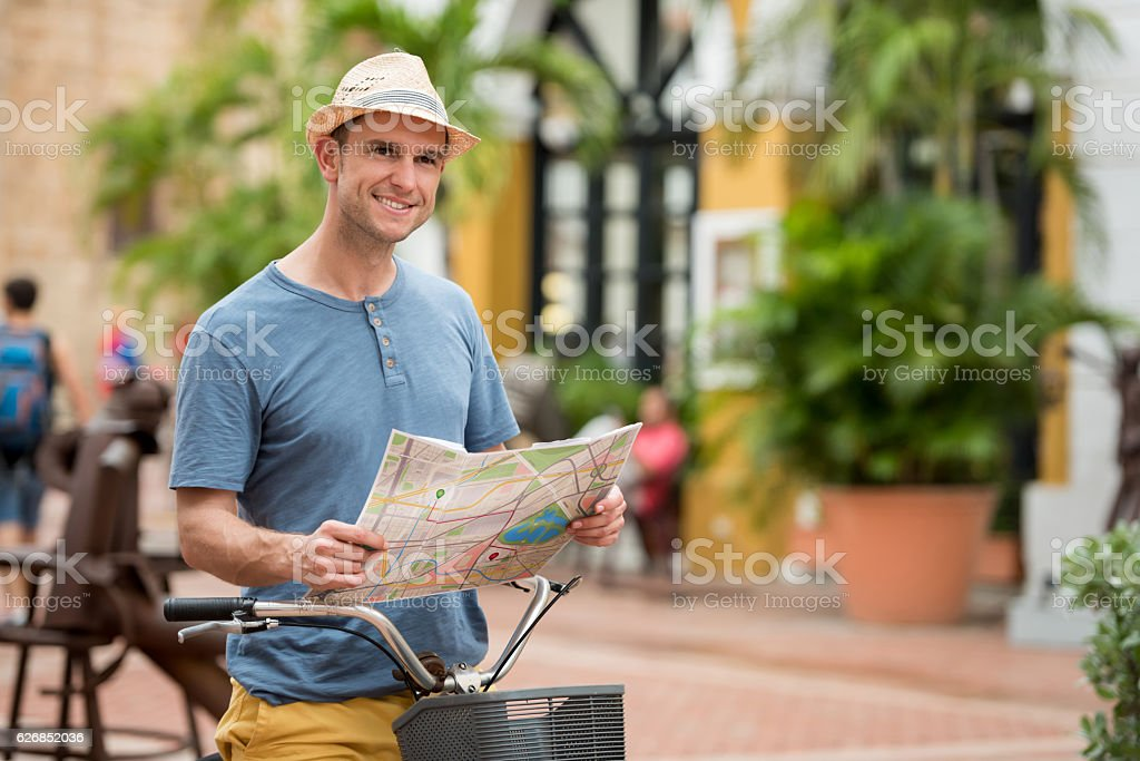 Tourist on a bike looking at a map stock photo