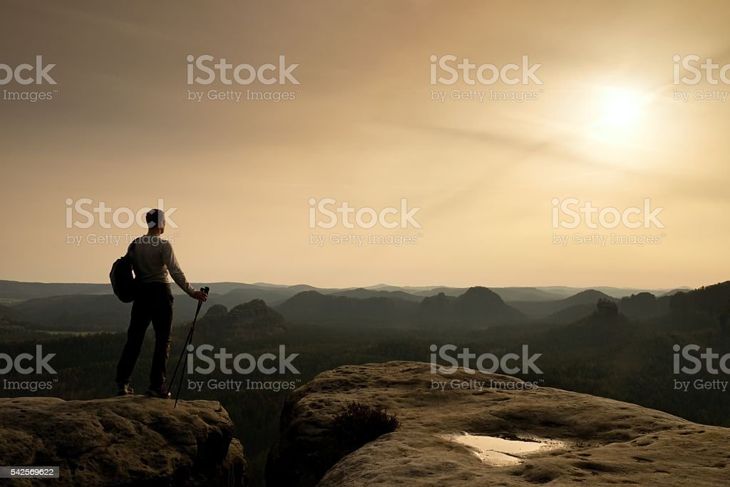 Tourist on cliff edge with pole in hand and backpack stock photo
