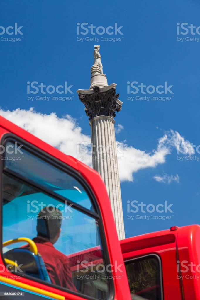 Tourist on red London double decker bus looking at Nelsons Column in Trafalgar Square London, England stock photo