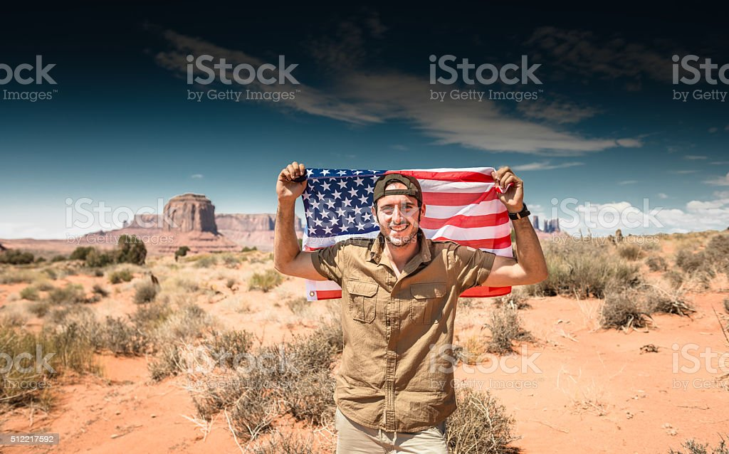 Tourist on the Monument valley with US flag stock photo