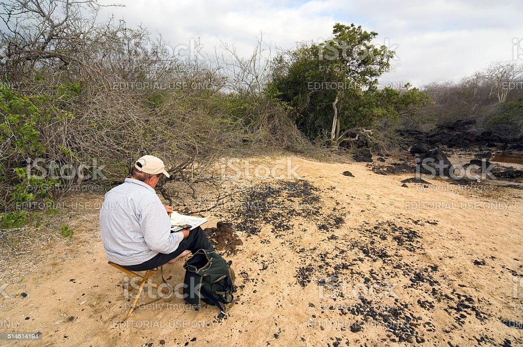 Tourist painting landscape on Mosquera island, Galapagos stock photo
