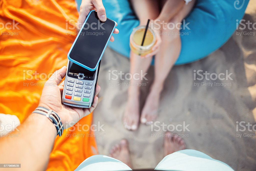 Tourist paying for cocktail with mobilephone stock photo