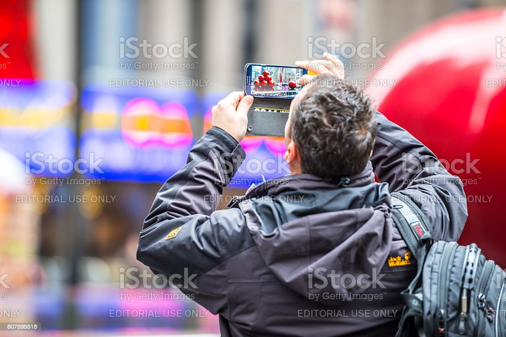 Tourist photographing NYC Christmas decorations on mobile phone stock photo