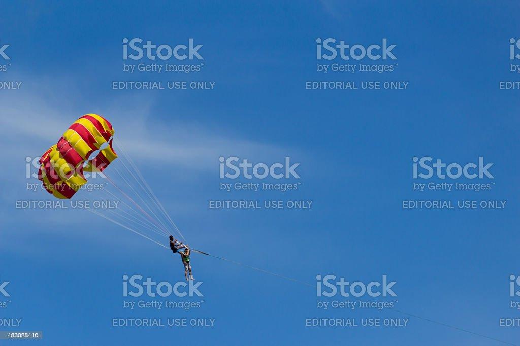 """Jogar parasail sobre a praia com céu azul fundo"""""""" foto royalty-free"""