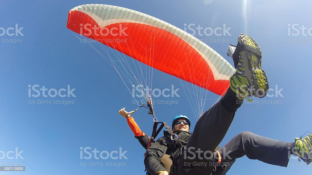 Tourist playing paragliding guided by a pilot stock photo