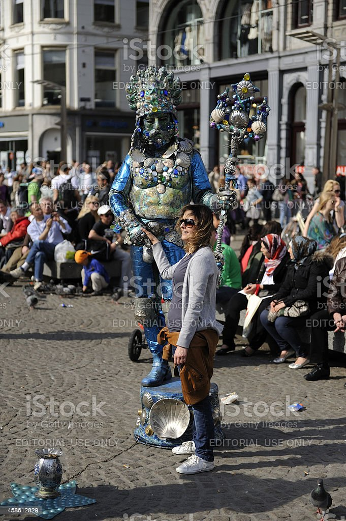 Tourist posing with man dressed as Neptunus in Amsterdam royalty-free stock photo