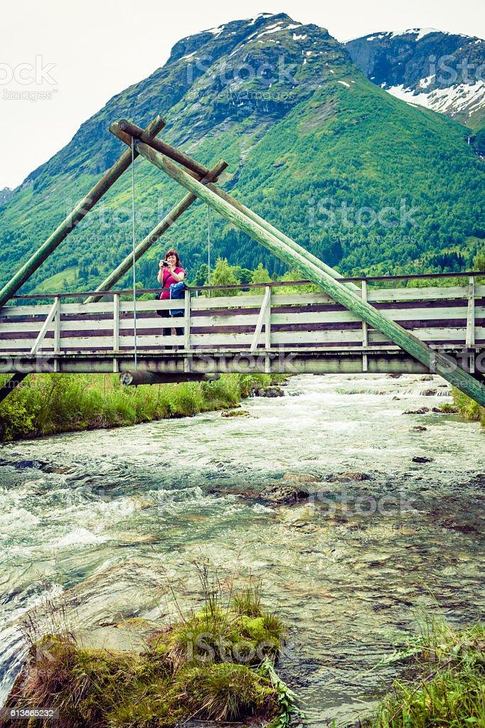 Tourist relaxing on bridge in village Oppstryn Norway stock photo