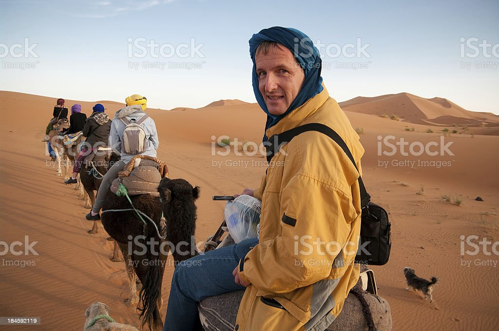 Tourist riding camel train in Sahara Desert, Africa stock photo