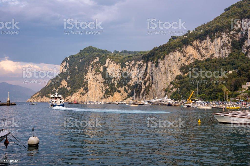 Tourist ship leaving Capri Island at sunset stock photo