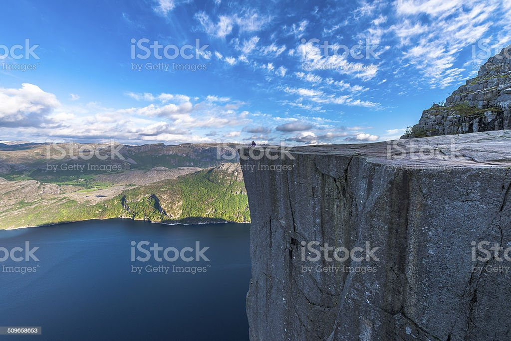 Tourist sitting at Famous Pulpit Rock edge in Norway stock photo