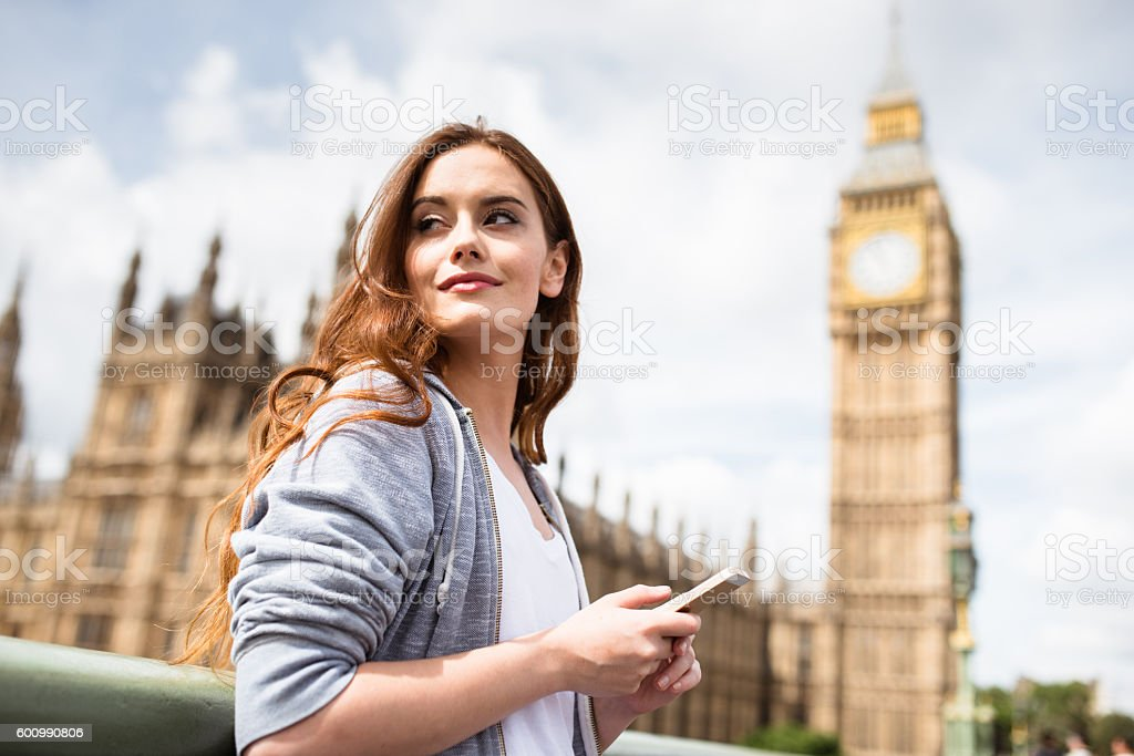 tourist smiling in London on the phone stock photo