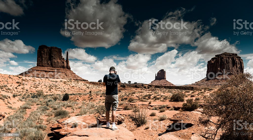 tourist standing against the monument valley landscape stock photo