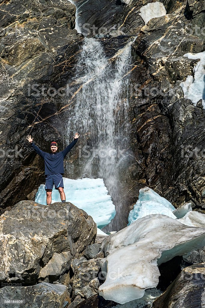 Tourist standing next to a waterfall stock photo