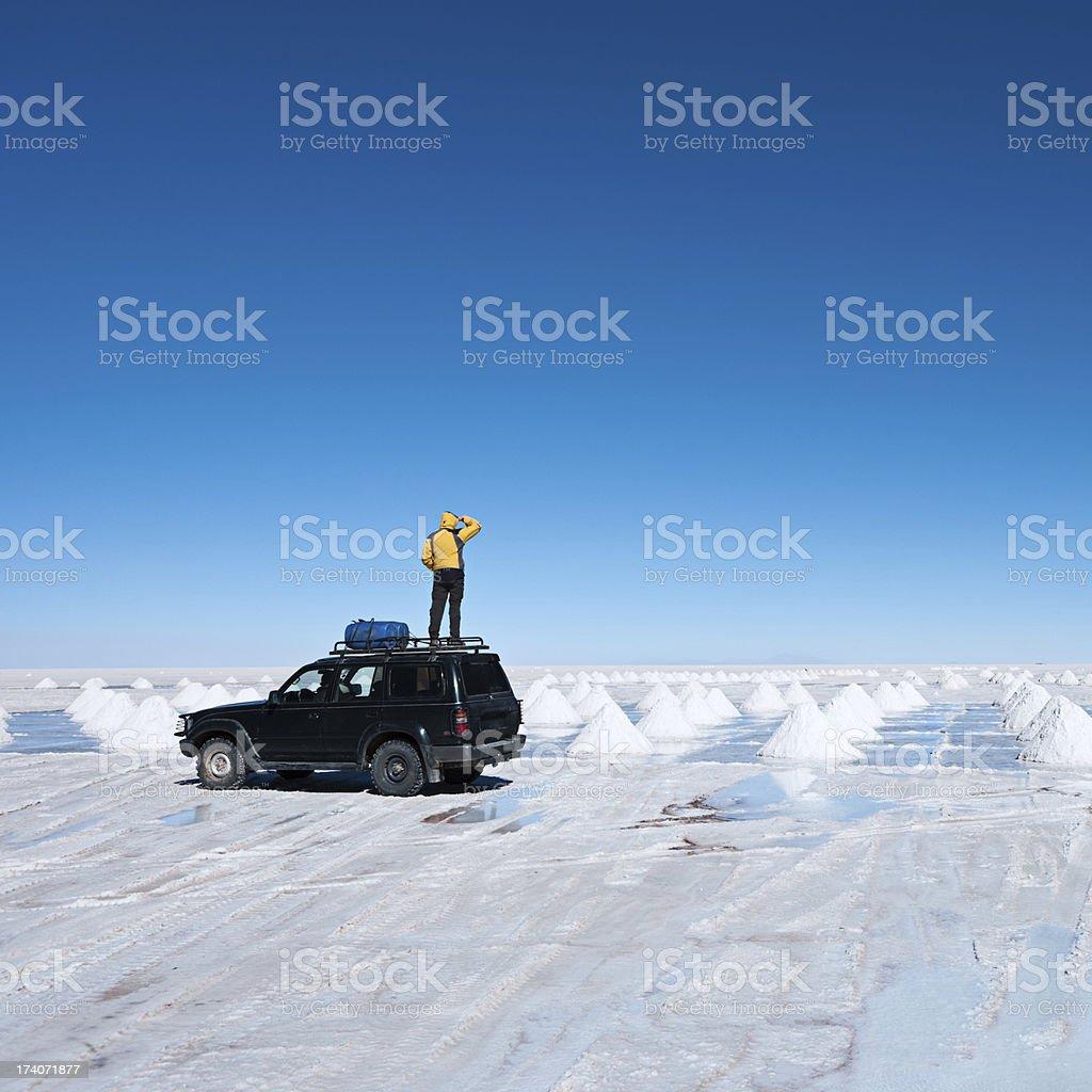 'Tourist standing on Salar de Uyuni, Altiplano Bolivia' stock photo