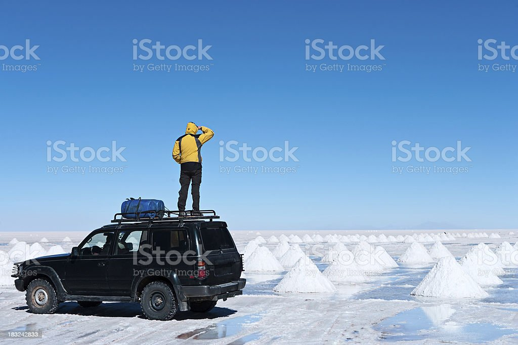 Tourist standing on Salar de Uyuni, Altiplano Bolivia stock photo