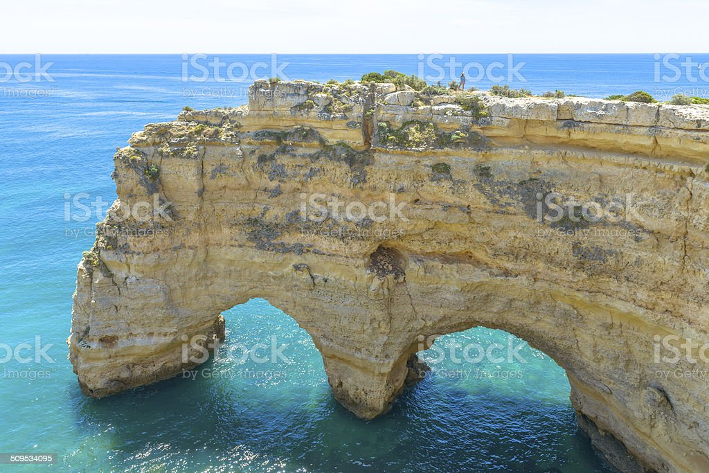 Tourist standing on top of a sea arch in Portugal stock photo