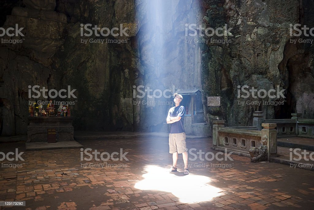 Man standing under ray of light in Marble Mountains, Vietnam royalty-free stock photo