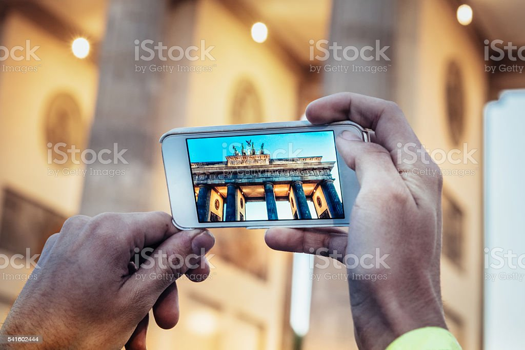 tourist takes photo of Brandenburger Tor with smartphone stock photo