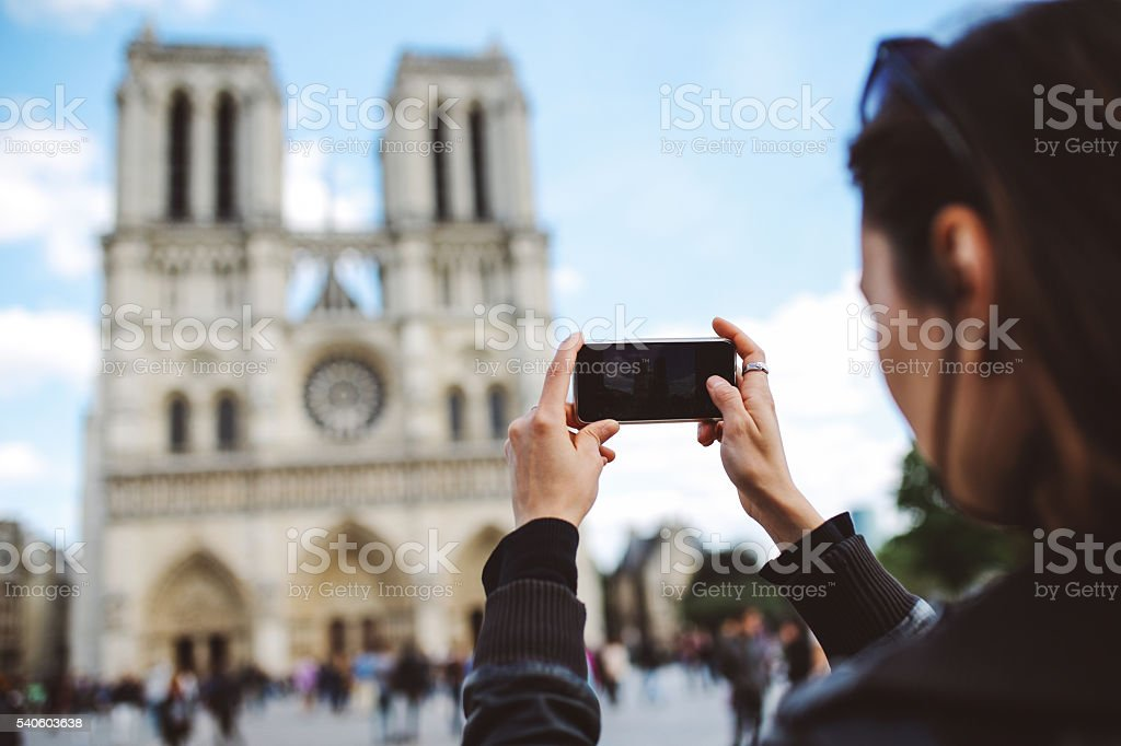 Tourist taking a photo of Notre Dame church in Paris stock photo